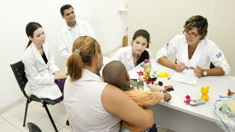 atendimento Clínico no consultório do Hoaspital Santa Casa. à mesa - residente de medicina atende  mãe e criança. O atendimento é acompanhado por três residentes de psicologia.